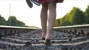 Jong blootvoets meisje die op spoorweg weglopen stock video
