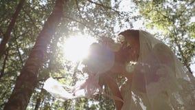 Jong bruid het snuiven huwelijksboeket bij hout stock videobeelden