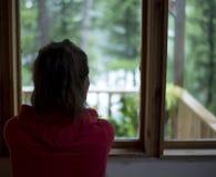 Jong bruin haired wijfje die uit huisvenster bos op een regenachtige dag bekijken stock afbeelding