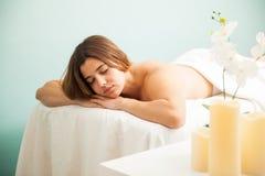 Jong brunette die een dutje nemen bij het kuuroord stock afbeelding