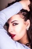 Jong brunette die haar haar houden Stock Afbeeldingen