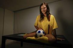 Jong brunette in gele voetbaluitrusting stock foto