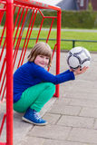 Jong buigend meisje met bal in rood metaaldoel Stock Foto's