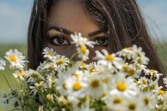 Jong charmant donkerbruin meisje met een boeket van witte gebiedskamilles op een de zomer zonnige dag royalty-vrije stock foto's