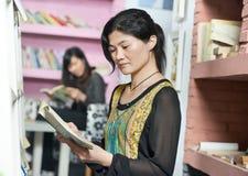 Jong Chinees studentenmeisje met boek in bibliotheek Royalty-vrije Stock Afbeelding