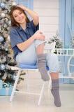 Jong chritmasmeisje met lang blondehaar die blauwe overhemdszitting op de stoel dragen stock afbeeldingen