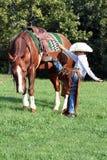 Jong cowboy het opzetten paard royalty-vrije stock fotografie