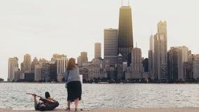 Jong creatief paar op de kust van het meer van Michigan, Chicago, Amerika De vrouw trekt, ma spelgitaar liggend op kust stock videobeelden