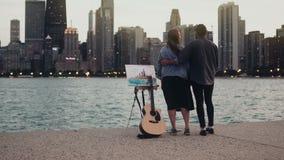 Jong creatief paar op de kust van het meer van Michigan, Chicago, Amerika Vrouwentekening, man die de gitaar in avond houden stock videobeelden