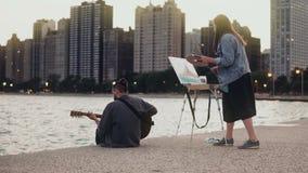 Jong creatief paar van straatkunstenaars die hobby op kust van Michigan, Chicago, de V.S. doen De vrouw trekt, man spelengitaar stock footage