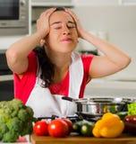 Jong de holdingshaar van de vrouwenchef-kok in frustratie, afgeraden gelaatsuitdrukking, lijst met ketel en groenten stock foto