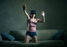 Jong de laag van de vrouwen thuis bank het spelen videospelletje die virtuele de werkelijkheidsbeschermende brillen gebruiken die Royalty-vrije Stock Afbeelding