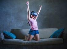 Jong de laag van de vrouwen thuis bank het spelen videospelletje die virtuele de werkelijkheidsbeschermende brillen gebruiken die Royalty-vrije Stock Fotografie