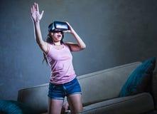Jong de laag van de vrouwen thuis bank het spelen videospelletje die virtuele de werkelijkheidsbeschermende brillen gebruiken die Royalty-vrije Stock Afbeeldingen