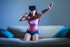 Jong de laag van de vrouwen thuis bank het spelen videospelletje die virtuele de werkelijkheidsbeschermende brillen gebruiken die Stock Fotografie