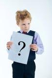 Jong die het vraagtekenteken van de jongensholding op witte achtergrond wordt geïsoleerd Stock Fotografie