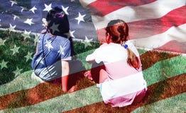 Jong die meisje twee in Amerikaanse vlag wordt verpakt De achtergrond van de onafhankelijkheid Day stock foto