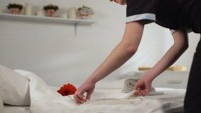 Jong dienstmeisje die en handdoeken vouwen nemen die weg, hotelruimte voor gasten schoonmaken stock footage