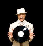 Jong DJ dat in wit kostuum vinylverslag binnen houdt Royalty-vrije Stock Fotografie