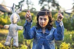 Jong donker-haired meisje in een denimjasje met een oud stuk speelgoed Royalty-vrije Stock Foto's