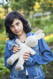 Jong donker-haired meisje in een denimjasje met een oud stuk speelgoed in de handen Royalty-vrije Stock Afbeelding