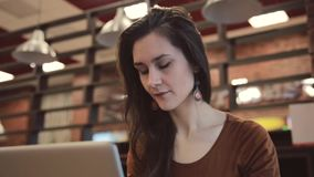 Jong donkerbruin meisje die aan laptop in koffie werken stock video