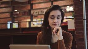 Jong donkerbruin meisje die aan laptop in koffie werken die dreamily zorgvuldig uit het venster kijken stock footage