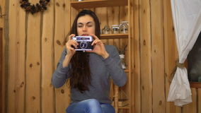 Jong donkerbruin meisje die foto op de retro camera thuis maken stock footage