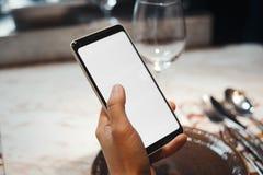 Jong donkerbruin meisje die mobiele telefoon houden terwijl het wachten van maaltijd De nadruk is op handen en mobiel royalty-vrije stock afbeelding