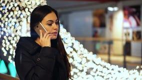 Jong donkerbruin meisje die op de telefoon in winkelcomplex op de achtergrond van het gloeien lichten spreken stock video