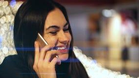 Jong donkerbruin meisje die op de telefoon in winkelcomplex op de achtergrond van het gloeien lichten spreken stock videobeelden
