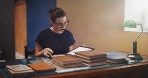 Jong donkerbruin meisje met glazen en het zwarte boek van de lippenstiftlezing royalty-vrije stock afbeelding