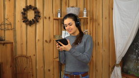 Jong donkerbruin meisje met hoofdtelefoons het luisteren muziek van tablet stock videobeelden