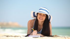 Jong donkerbruin meisje met nota en potlood stock videobeelden
