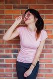 Jong donkerbruin meisje met zonnebril op bakstenen muurachtergrond stock fotografie