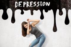 Jong donkerbruin meisje toevallige jeans dragen en t-shirt die beschermen met handen tegen zwart DEPRESSIEteken op wit royalty-vrije stock afbeelding