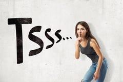Jong donkerbruin meisje toevallige jeans dragen en t-shirt die stil die gebaar met TSSS-teken tonen op witte achtergrond wordt ge stock fotografie