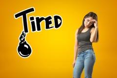 Jong droevig donkerbruin meisje toevallige jeans en t-shirt met VERMOEID teken dragen en zwarte geketende die bal die op geel wor stock foto's