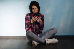 Jong droevig meisje die aan afhankelijkheid van sociale netwerken lijden die op de vloer met een smartphone zitten royalty-vrije stock foto