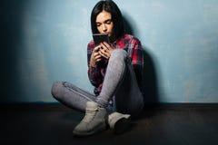 Jong droevig meisje die aan afhankelijkheid van sociale netwerken lijden die op de vloer met een smartphone zitten royalty-vrije stock foto's