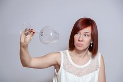 Jong droevig mooi meisje die een leeg transparant kristal omgekeerd wijnglas houden Het Sommelierconcept, beëindigt wijn, alcohol royalty-vrije stock fotografie