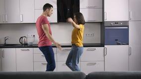 Jong echtpaar die in de keuken dansen stock videobeelden