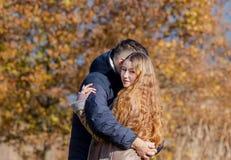 Jong echtpaar die in het de herfstpark koesteren royalty-vrije stock foto