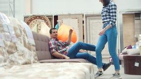 Jong echtpaar in een meubilairopslag stock footage