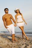 Jong elegant paar dat op de kust loopt stock foto