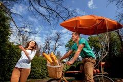Jong en blij paar die pret in het park met fiets hebben en royalty-vrije stock afbeelding