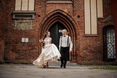 Jong en gelukkig echtpaar die in een yard van de oude uitstekende rode baksteenbouw lopen royalty-vrije stock foto's