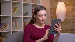 Jong en mooi donkerbruin wijfje die freelancer met en interessante tablet werken die thuis worden geconcentreerd stock videobeelden