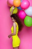 Jong en mooi krullend meisje in een gele kleding op een roze achtergrond die kleurrijke ballons houden Royalty-vrije Stock Fotografie