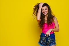 Jong en mooi krullend meisje in een roze overhemd en blauwe borrels o Stock Afbeelding